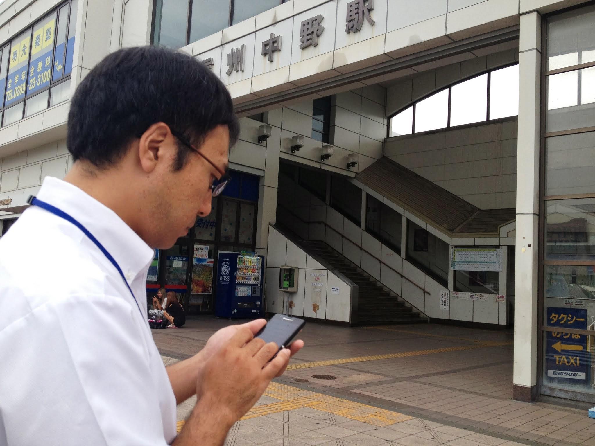 スマートフォンでガイドを作成する広報係の市職員