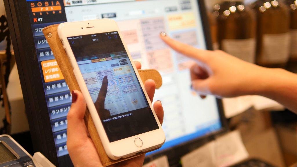 株式会社MASHUにおけるスマートフォンでTeachme Bizを参照しながらのレジ業務場面