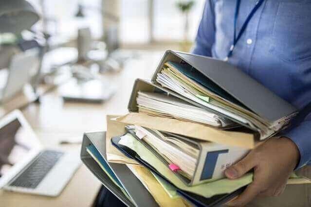 書類を抱える男性の画像