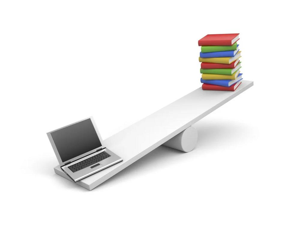 パソコンと本がシーソーに乗っている画像