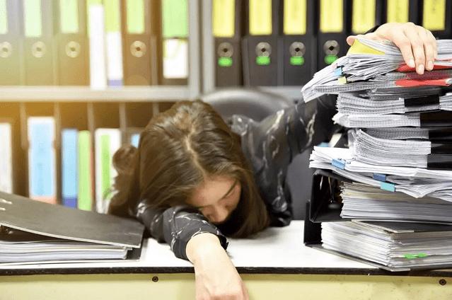 書類の中で居眠りする人の画像