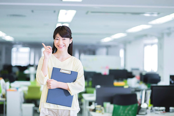 オフィスの中でバインダーを持つ女性の画像