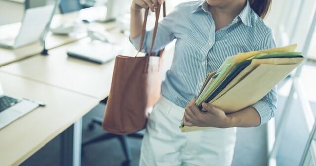 女性が書類とバッグを抱える画像