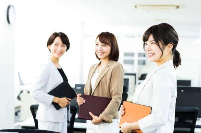 女性3人が職場で笑顔の画像
