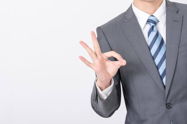 スーツ姿の男性がOKマークを指で作る画像