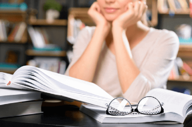 テーブルの上に眼鏡と本がある画像