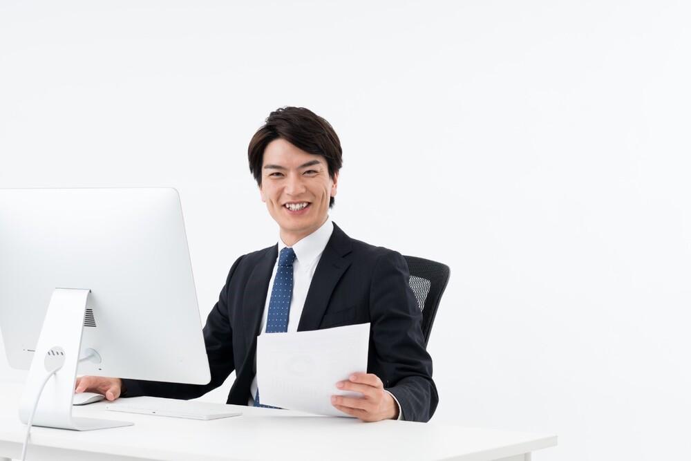 男性がパソコンの前で仕事をする画像