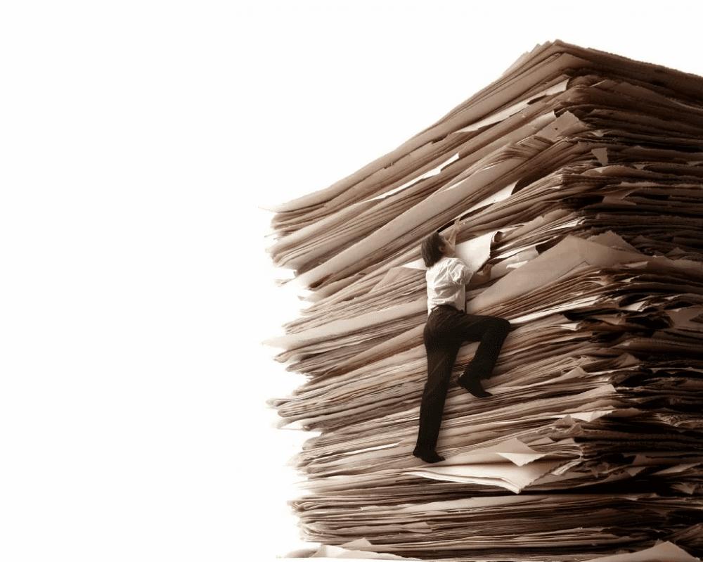 積み重なった書類をよじ登る人の画像