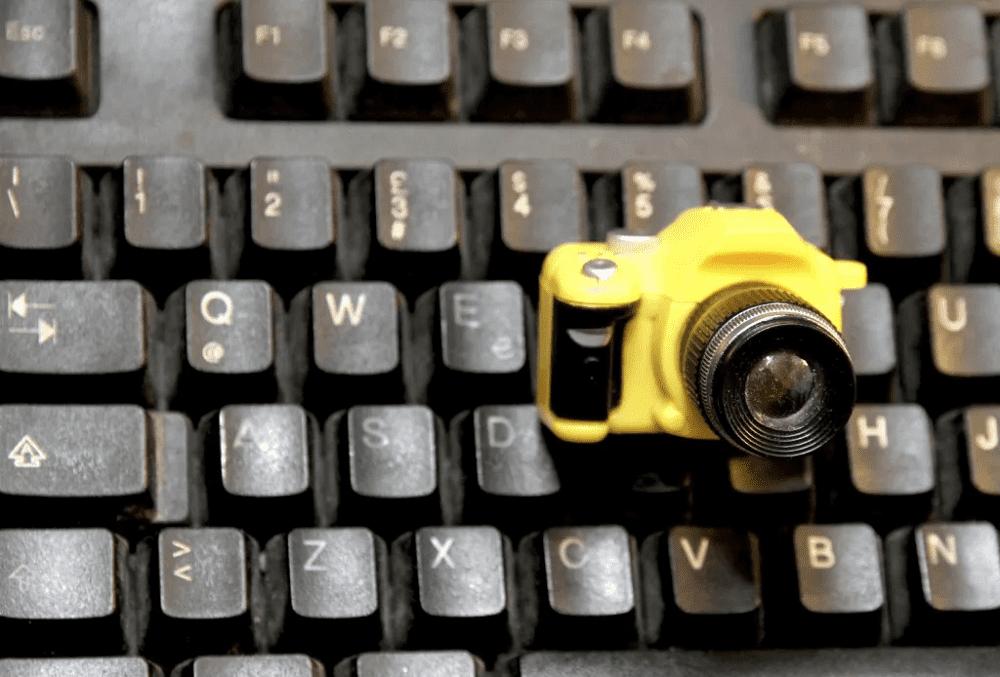 パソコンのキーボードの上に乗った小さなカメラの画像