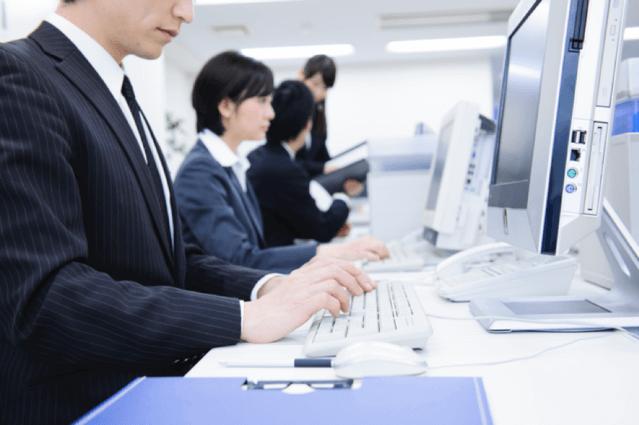 PCに向かって働く人の画像