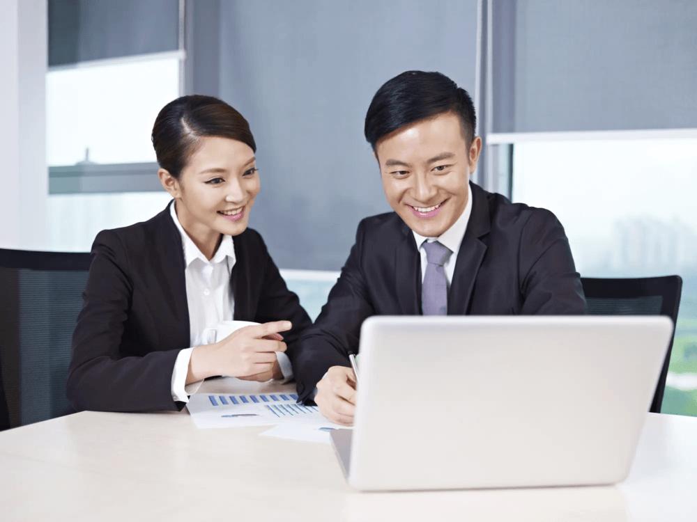 笑顔でパソコンを見る男女の画像