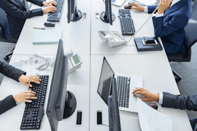 机を挟んで働く人の画像