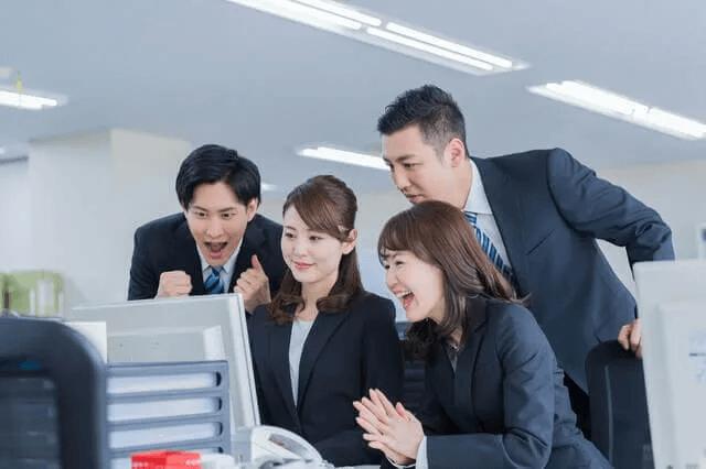 パソコンを見て笑顔になる人々の画像