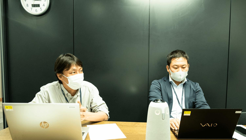 男性二人がパソコンの前で話す画像