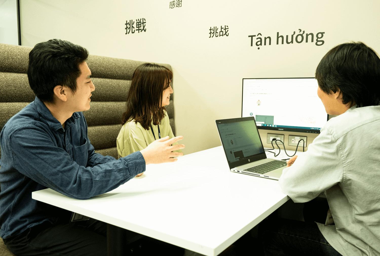 男女3人がモニターの前で会議する画像